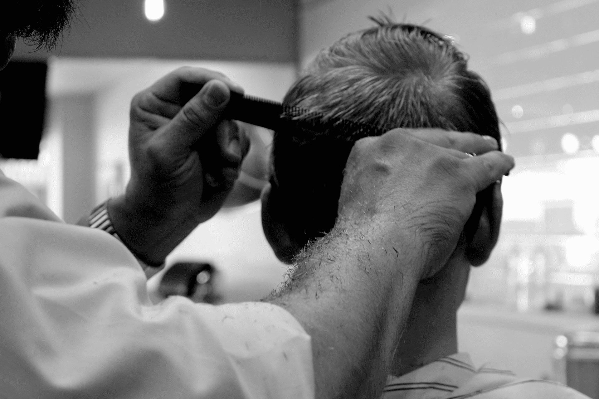 Cortando el pelo a un hombre en una peluquería.